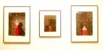"""Galeriebesucher spiegeln sich in den hinter Glas gezeigten Arbeiten der Serie """"Die rote Wüste"""". Farah Willem — hier: Bürgergalerie Neumünster eV."""